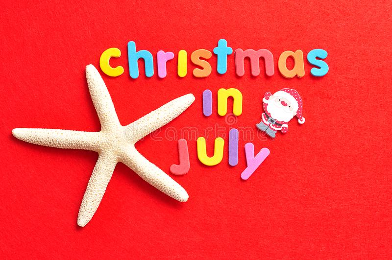 The words christmas in July in colorful letters with a starfish and a Santa figurine stock photography