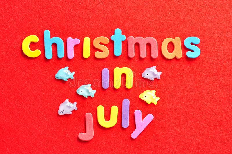 The words christmas in July on a red background and dolphins figurines stock image