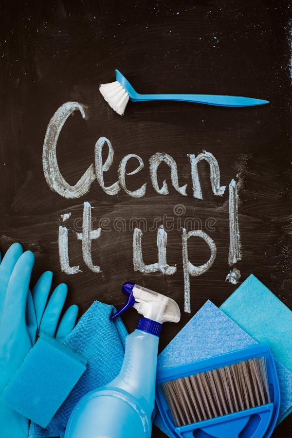 The words `clean it up!`on the chalkboard above the blue spring cleaning kit. The words `clean it up!`on the chalkboard above the blue spring cleaning kit royalty free stock photo