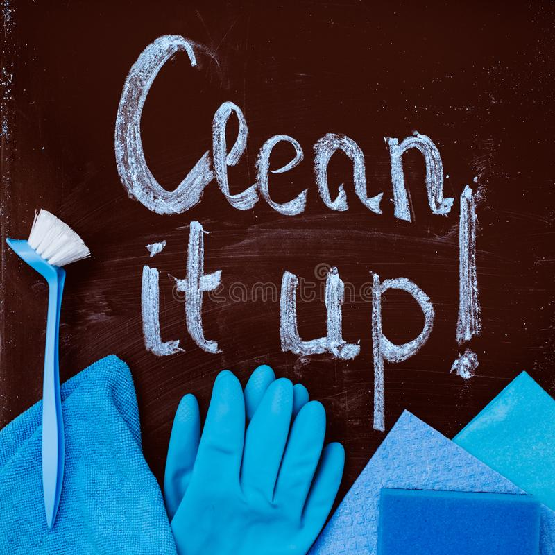 The words `clean it up!`on the chalkboard and spring cleaning kit. The words `clean it up!`on the chalkboard above the blue spring cleaning kit royalty free stock photo