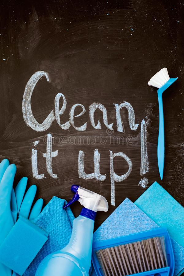 The words `clean it up!`on the chalkboard and spring cleaning kit. The words `clean it up!`on the chalkboard above the spring cleaning kit royalty free stock photography
