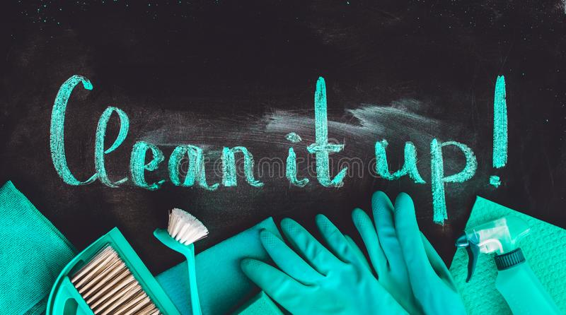 The words `clean it up!`on the chalkboard above the spring cleaning kit. The words `clean it up!`on the chalkboard above the spring cleaning kit stock images
