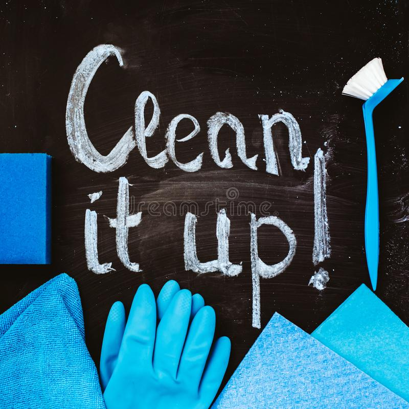 The words `clean it up!`on the chalkboard above the spring cleaning kit. The words `clean it up!`on the chalkboard above the spring cleaning kit royalty free stock image
