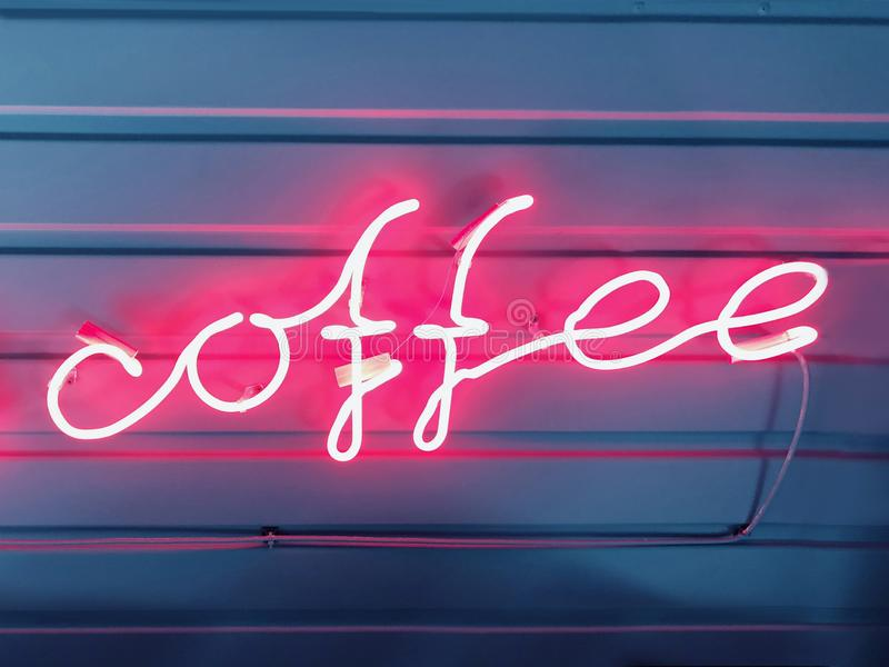 Words of coffee from a neon tube pink glow. Neon sign, word coffee from a neon tube pink glow on a dark blue background. Design element. Image stock image