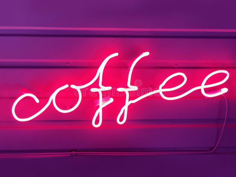 Words of coffee from a pink neon tube. Neon sign, word coffee from a pink neon tube on a dark purple background. Design element. Image royalty free stock image