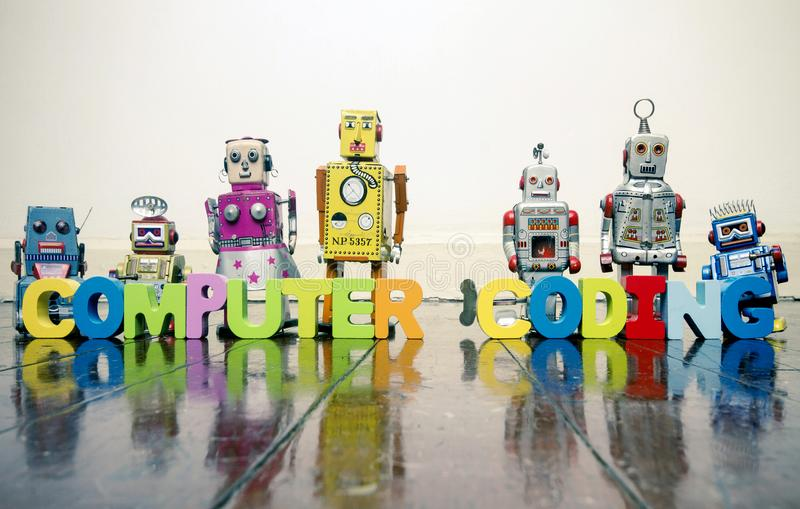 the words COMPUTER CODING with wooden letters and retro toy robots on an old wooden f stock images