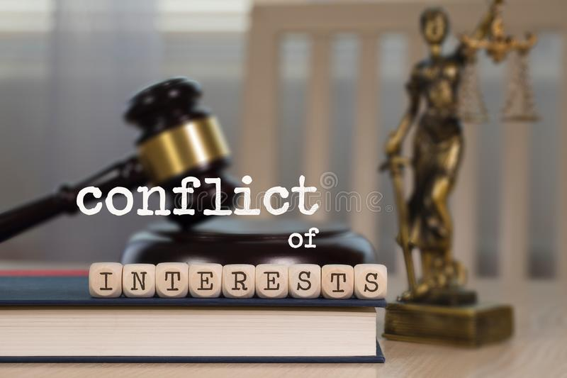 Words CONFLICT OF INTERESTS composed of wooden dices. Wooden gavel and statue of Themis in the background stock image
