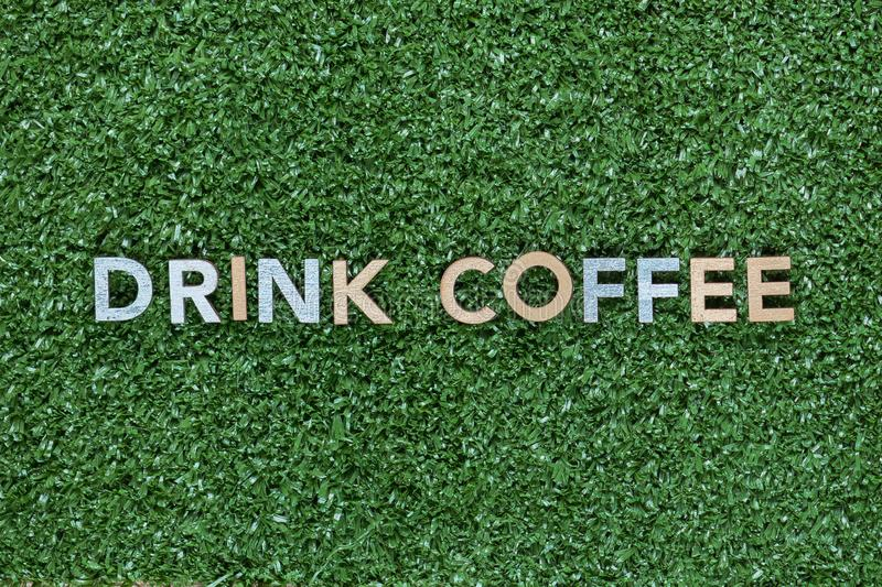 The words Drink coffee made from multicolored letters on grass background, shot from above, aligned in the center. The words Drink coffee made from multicolored stock photography