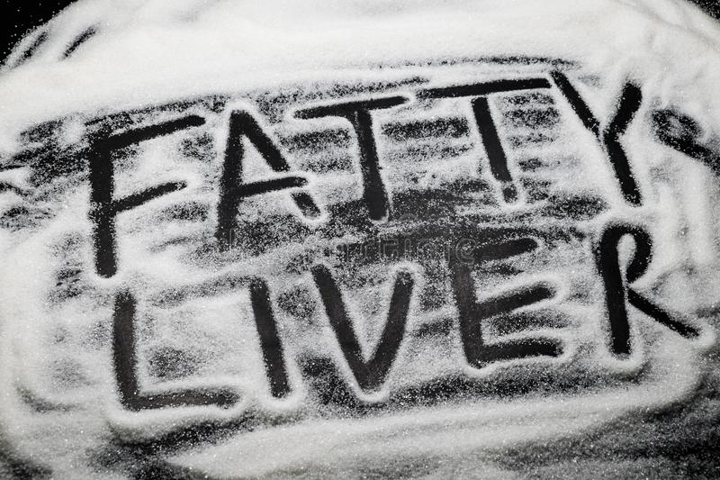 Words Fatty Liver written with and in sugar grains, sugar is know to cause fatty liver disease royalty free stock photos