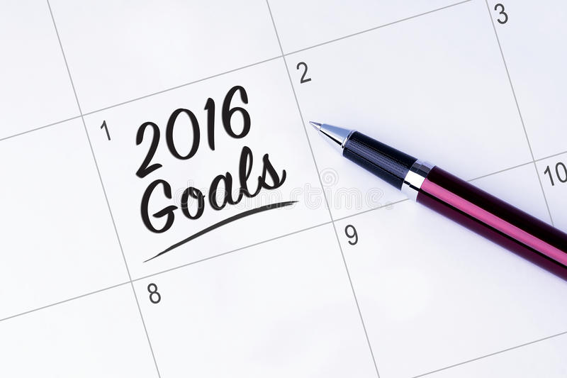 The words 2016 Goals on a calendar planner to remind you an important appointment with a pen on isolated white background. New Ye royalty free stock images