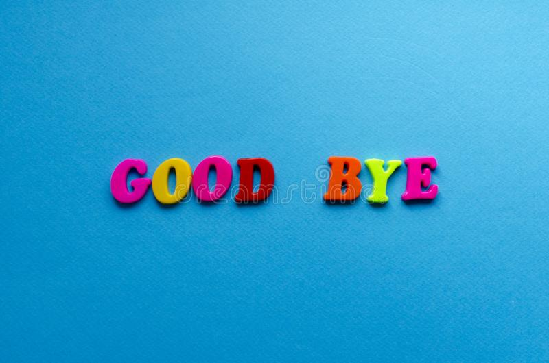Words good bye from plastic magnetic letters on blue background stock image