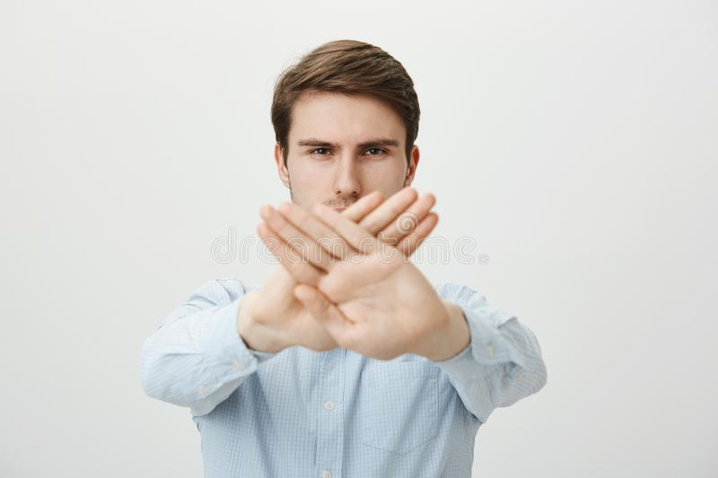 Without words. Good-looking serious self-assured caucasian guy in casual shirt pulling crossed palms towards camera and. Over mouth, warning, showing stop or no stock image
