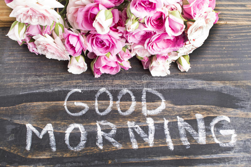 Words Good Morning with Pink Roses on a Rustic Wooden Background royalty free stock image