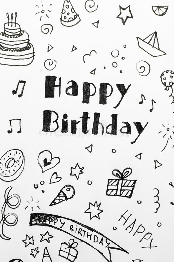 Words HAPPY BIRTHDAY and funny little pictures on white paper. Top view stock image