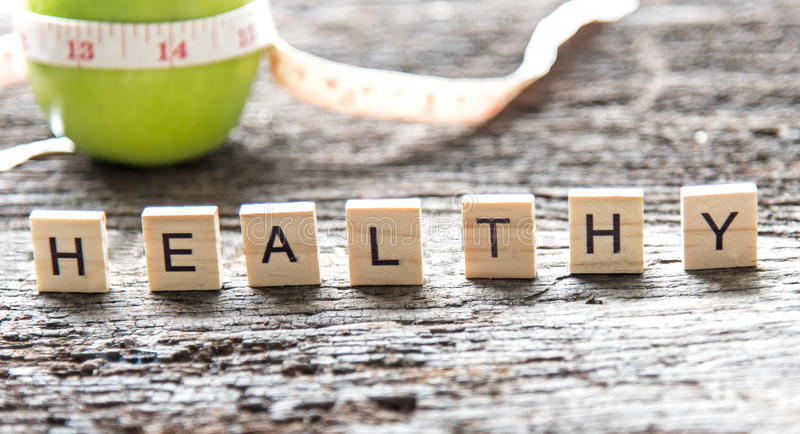 Words of Healthy concepts collected in crossword with wooden cubes. Green apple and measuring tap background. royalty free stock photos