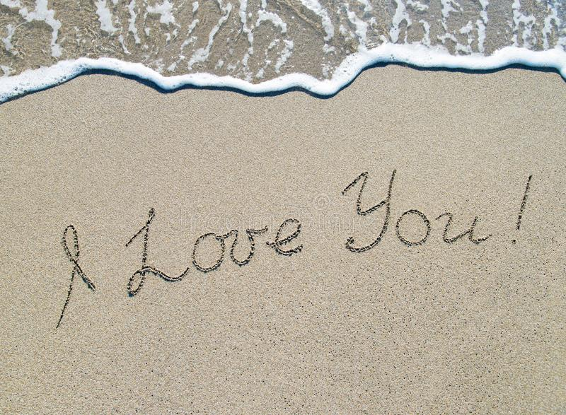 Words I love you outline on sand with wave brilliance royalty free stock photos