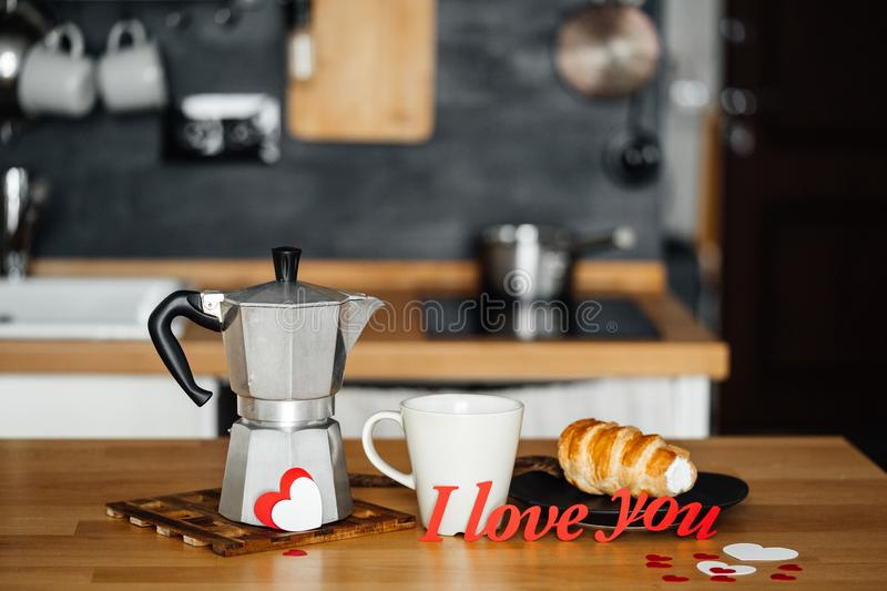 Words I LOVE YOU from red paper on the table with a coffee maker mug and cake on a plate against the background of home kitchen in stock photos