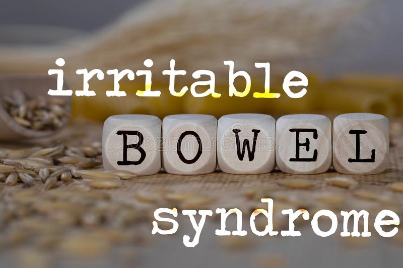 Words IRRITABLE BOWEL SYNDROME composed of wooden dices. Rye grains in the background. Closeup, allergen, deficiency, allergy, autoimmune, disorders, celiac stock photos