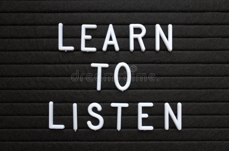 The phrase Learn To Listen in white letters on a notice board royalty free stock photography