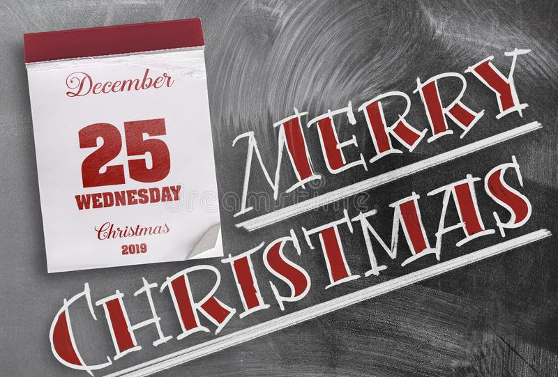 Merry Christmas on chalkboard with tear-off calendar on December 25. Words Merry Christmas on chalkboard with tear-off calendar on December 25 stock image