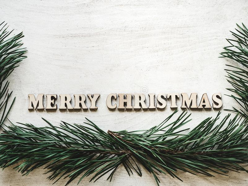 Words MERRY CHRISTMAS and green Christmas tree. Letters of the alphabet in the form of the words MERRY CHRISTMAS and green Christmas tree branches on a white royalty free stock image