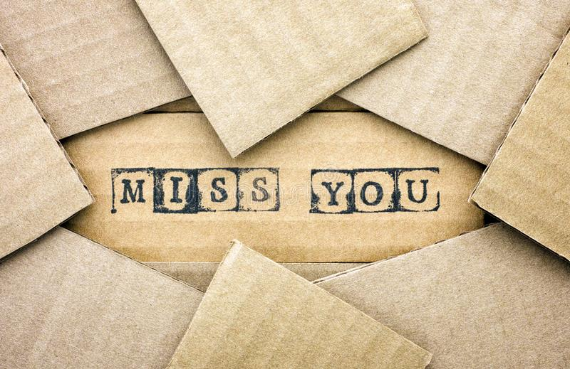 Words Miss You make by black alphabet stamps on cardboard stock photo