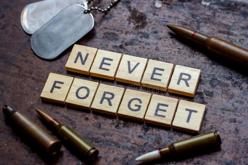 The words never forget with bullets  and old and worn military dog tags on rusty metal background. The words never forget with bullets  and old and worn stock photos