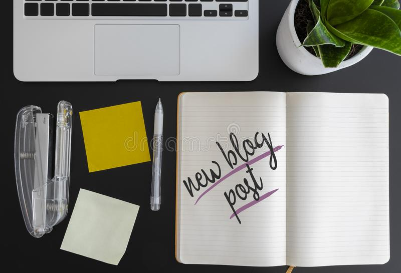 Words new blog post written on note pad on desk next to laptop and adhesive notes royalty free stock photos