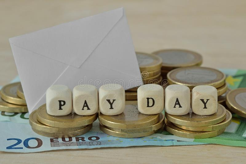 Words Pay day written with wood cubes over euro coins and banknotes.  royalty free stock photography
