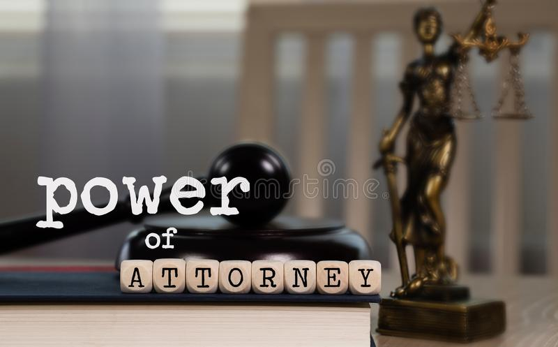 Words POWER OF ATTORNEY  composed of wooden dices. Wooden gavel and statue of Themis in the background. Closeup, ancient, greek, titaness, book, chair, concept stock photos