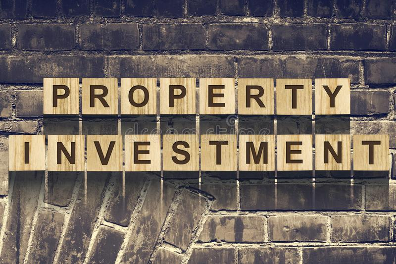 Words, Property Investment, consisting of letters on wooden construction cubes against the background of an old vintage stock image
