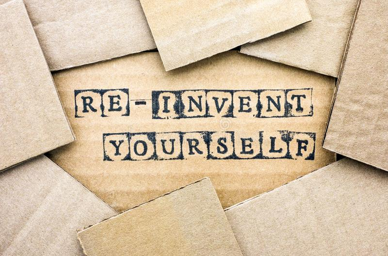 Words Re-invent Yourself make by black alphabet stamps on cardboard. With some piece of cardboard royalty free stock image