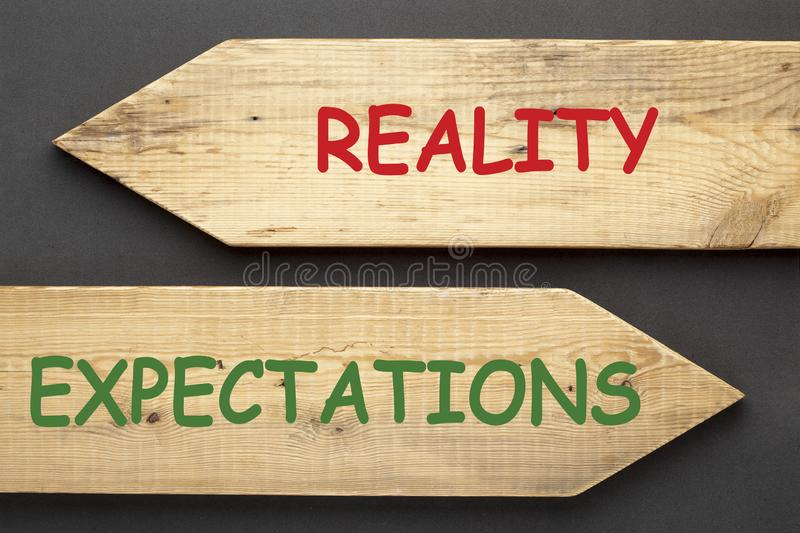 Reality Expectations Concept. The words Reality vs. Expectations written on old wooden arrows on black background stock photos