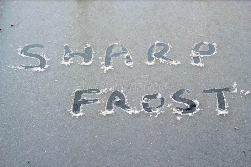 Words sharp frost written into ice on a window. The words sharp frost written into the cold ice on a window pane of glass. Winter time stock photography
