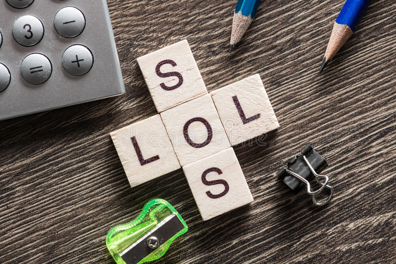 Words SOS and LOL on table made of wooden cubes elements. Crossword collected of cubes and spelling word SOS and LOL stock images