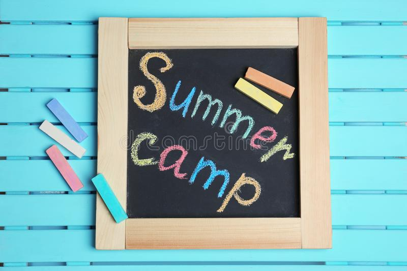 Words SUMMER CAMP written with colorful chalk. On small blackboard, top view royalty free stock images