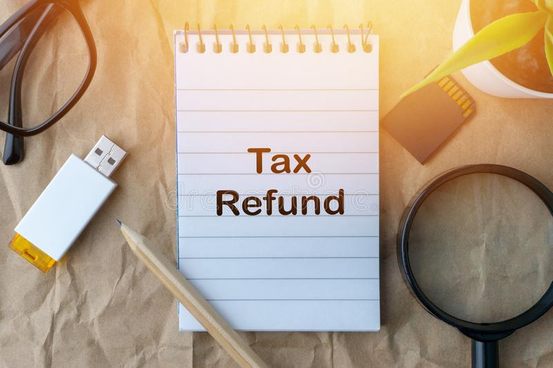 Words TAX REFUND on wooden paper background. Business and education concept stock image