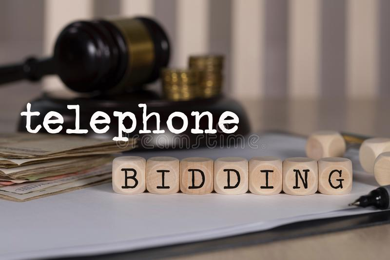 Words TELEPHONE BIDDING composed of wooden dices. Auction gavel on the table in the background. Closeup, coins, money, finance, auctioneer, bids, business stock photos