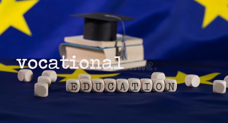 Words  VOCATIONAL EDUCATION composed of wooden letters. Black graduate hat on EU flag in the background. Closeup royalty free stock photo