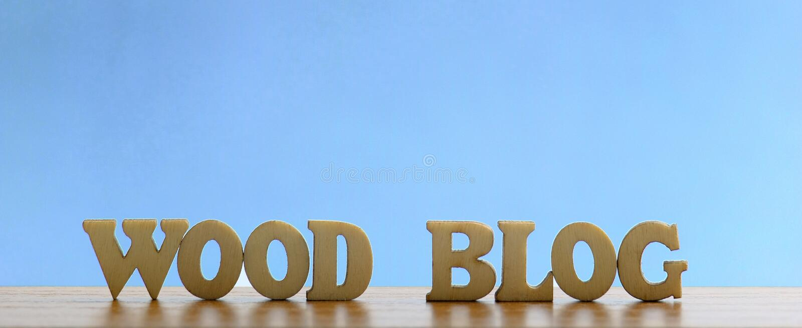 The words WOOD BLOG are made of wooden letters on a blue background. The space above is for an inscription or logo. royalty free stock photography