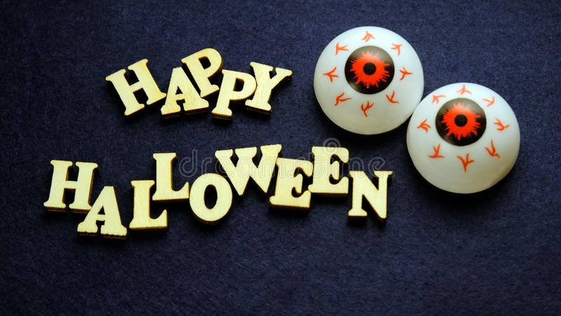 HAPPY HALLOWEEN and two balls of eye on a dark blue background. Words of wooden letters. Emotional decoration for the holiday. Words of wooden letters. HAPPY royalty free stock image