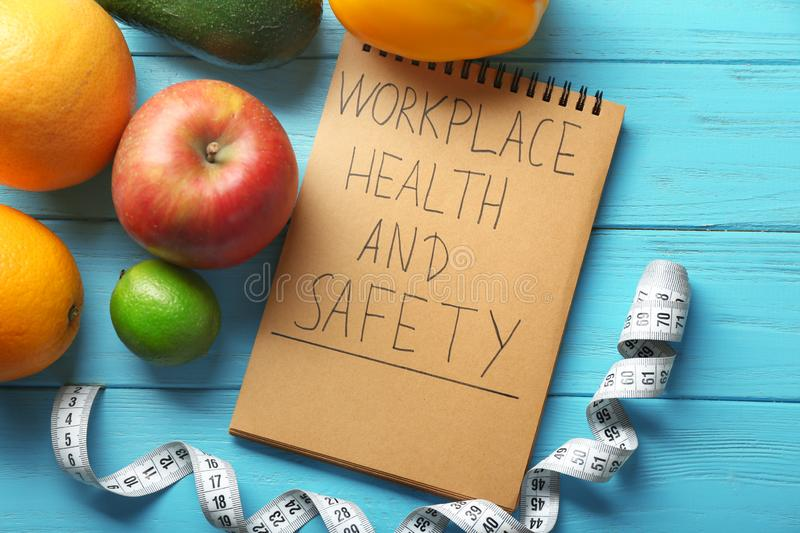 Words \'Workplace, health and safety\' written in notebook, fruits and measuring tape on wooden background royalty free stock photos
