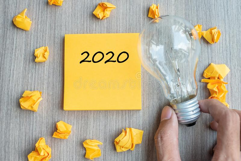 2020  words on yellow note and crumbled paper with Businessman holding lightbulb on wooden table background. New Year New Idea stock photography