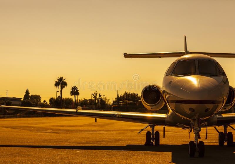 Wordt de luxe privé straal geparkeerd op een vliegveld tijdens schitterende gouden zonsondergang stock foto