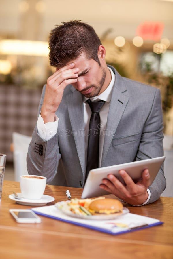Woried y hombre de negocios subrayado en el descanso para tomar café que trabaja en h foto de archivo libre de regalías