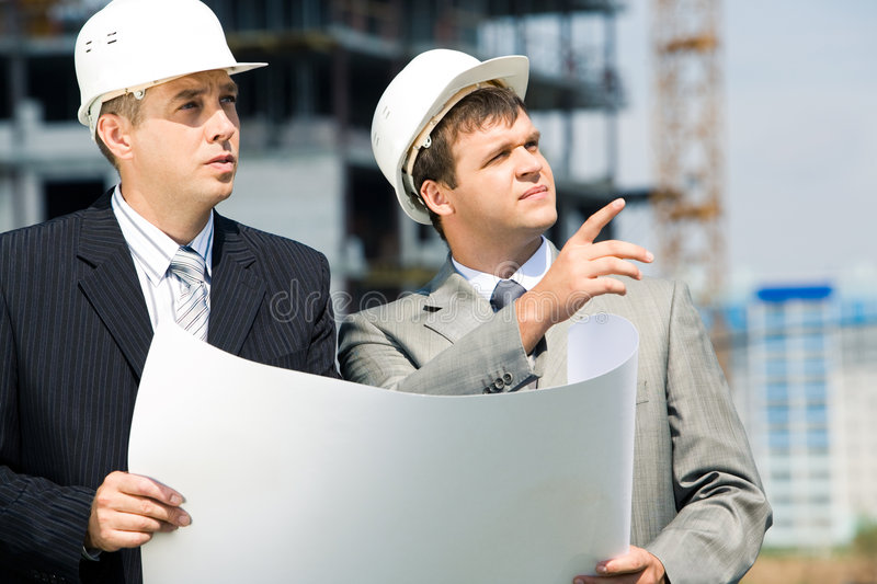At work. Portrait of successful workers holding a project and discussing a building place royalty free stock photos