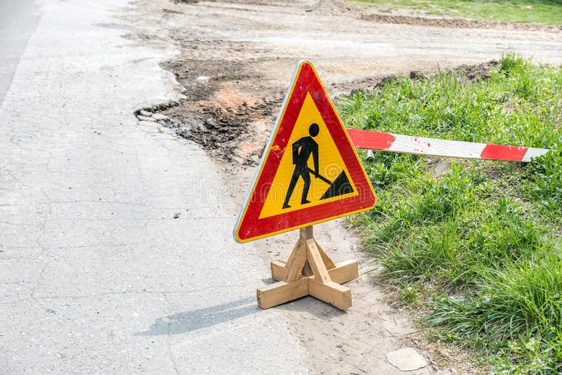 Work ahead caution or warning traffic road sign on the street to warn drivers of reconstruction or reparation of the asphalt stock photos