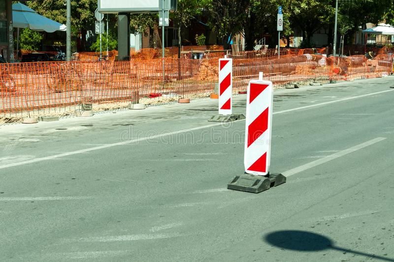 Work ahead street reconstruction site with sign and fence as road barricade. Work ahead street construction and reconstruction site with warning sign dead end royalty free stock photos