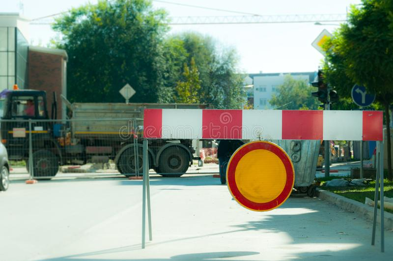 Work ahead street reconstruction site with sign and fence as road barricade. Work ahead street construction and reconstruction site with warning sign dead end royalty free stock photography