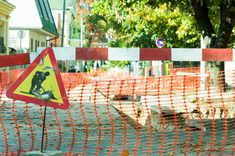 Work ahead street reconstruction site with sign and fence as road barricade. Work ahead street reconstruction site with sign and fence as road barricade royalty free stock image